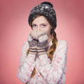 Beautiful red hair woman in winter outfit warm sweater scarf and hat with snow all over her isolated on pink red Royalty Free Stock Photos
