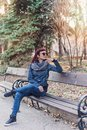 Beautiful red haired girl sitting on a bench in the park