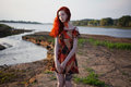 Beautiful red-haired girl in sundress standing on the background of the river Royalty Free Stock Photo