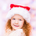 Beautiful red haired little girl with long curly hair wearing santa claus christmas hat closeup portrait of a and new Royalty Free Stock Image