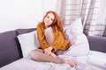 Beautiful red-haired woman curls herself comfortably on her couc Royalty Free Stock Photo