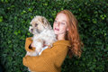 Beautiful red-haired woman has her dog on her arm Royalty Free Stock Photo