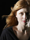 Beautiful red haired woman looking at camera closeup of on black background Stock Photo