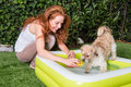 Beautiful red-haired woman plays with her dog by the pool Royalty Free Stock Photo