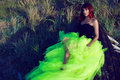 Beautiful red haired womanin black corset and long tail green veiling skirt lying on the shabby upside down wooden boat Royalty Free Stock Photo