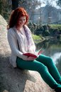 Beautiful red head young woman reading book in the park Stock Photo