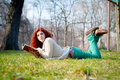 Beautiful red head young woman reading book in the park Stock Image