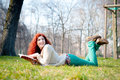 Beautiful red head young woman reading book in the park Royalty Free Stock Images