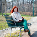 Beautiful red head young woman reading book in the park Stock Photos