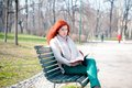 Beautiful red head young woman reading book in the park Stock Images