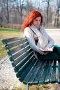 Beautiful red head young woman reading book in the park Royalty Free Stock Photos