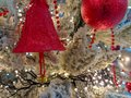 Beautiful red ornaments on Christmas tree during holiday season 2019 in shape of bell, ball and pearls, fake snow on the branches Royalty Free Stock Photo