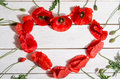 Beautiful red poppies in shape of heart on wooden background Royalty Free Stock Photography