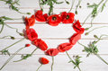 Beautiful red poppies in shape of heart on wooden background Royalty Free Stock Photos