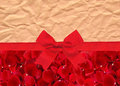 Beautiful red rose petals and red ribbon with bow over old paper Royalty Free Stock Photo