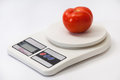 Beautiful red tomato on a white kitchen scale Royalty Free Stock Photo