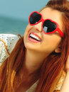 Beautiful redhaired girl in sunglasses on beach portrait holidays vacation travel and freedom concept happy heart shaped Stock Images