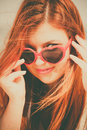 Beautiful redhaired happy girl in heart shaped sunglasses on beach holidays vacation travel and freedom concept Royalty Free Stock Image