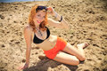 Beautiful redhead on a beach in black swimsuit and orange shorts lying in the sand glamour and pin up photography Stock Photos