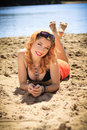 Beautiful redhead on a beach in black swimsuit and orange shorts lying in the sand glamour and pin up photography Royalty Free Stock Images