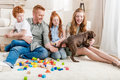 Beautiful redhead family with puppy playing with constructor on floor at home Royalty Free Stock Photo