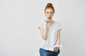 Beautiful redhead girl making notes thinking sitting over white background. Royalty Free Stock Photo