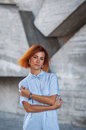 Beautiful redhead girl wearing in a striped shirt posing against background of concrete wall Royalty Free Stock Photo
