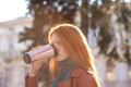 Beautiful redhead lady drinking coffee from tumbler young with long hair in leather jacket and scarf Stock Image