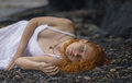 Beautiful redhead woman at the rocky beach in a white dress laid down on gravel Stock Photo