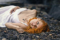 Beautiful redhead woman at the rocky beach in a white dress laid down on gravel Stock Photography