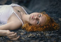 Beautiful redhead woman at the rocky beach in a white dress laid down on gravel Stock Image