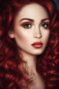 Beautiful redhead woman with wavy hair portrait of and green eyes looking at camera Royalty Free Stock Photography