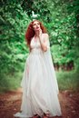Beautiful redhead woman wearing white dress in a forest the Royalty Free Stock Photo
