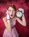 Beautiful redhead women with clock. Royalty Free Stock Photo