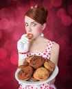 Beautiful redhead women with coockie woman photo in retro style bokeh at background Royalty Free Stock Image