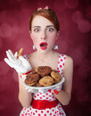 Beautiful redhead women with coockie woman photo in retro style bokeh at background Royalty Free Stock Photography