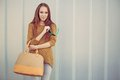 Beautiful redheaded girl with fashionable big bag standing near gray wall Royalty Free Stock Photo