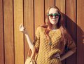 Beautiful redheaded girl with fashionable big bag in sunglasses standing near wooden wall warm tonning Royalty Free Stock Photography