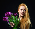 Beautiful redheaded girl hold bouquet of purple tulips flowers and happy looking at the corner on a white background Stock Image