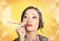 Beautiful reto lady smoking on yellow background asian with cigarette holder Royalty Free Stock Images