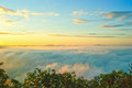 Beautiful rising sun in the early morning over sea of fog on hill of Phu Tok. Royalty Free Stock Photo