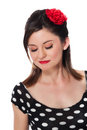 Beautiful rockabilly girl with closed eyes she is wearing a black and white polka dot shirt and red flower in her hair isolated on Stock Images