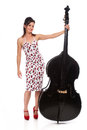 Beautiful rockabilly girl with double bass an attractive wearing a cherry print dress smiling and posing a shot in the studio and Stock Photo
