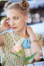 Beautiful romantic blonde girl in dress at table in cafe portrait of retro coffee shop on the street Royalty Free Stock Photos
