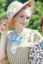 Beautiful romantic blonde girl in old straw hat portrait of retro dress and summer park Stock Image