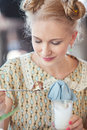 Beautiful romantic blonde girl in retro style eating cake with a from spoon at outdoor cafe Royalty Free Stock Photos