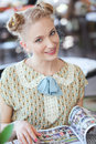 Beautiful romantic blonde girl in retro style portrait of dress with fashion magazine at street cafe Stock Image