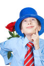 Beautiful romantic boy wearing a shirt a tie and blue hat holding a rose behind his back thinking love concept Royalty Free Stock Image
