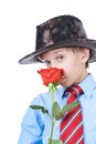 Beautiful romantic boy wearing a shirt and a tie holding red rose blond hat looking shy valentine concept Royalty Free Stock Photo