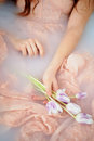Beautiful romantic red-haired girl sitting in the bath and holding flowers . The face is not visible. In lace dress Royalty Free Stock Photo